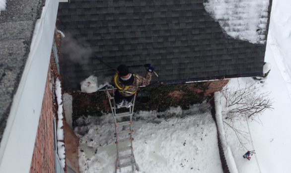 Commercial ice dam removal project. Man on ladder ice dam steaming